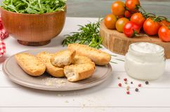 Vegetarian toasts with cream cheese, tomatoes, arugula, rosemary and black pepper on rustic wooden table.  stock photo
