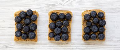 Vegetarian toasts with peanut butter, blueberries and chia seeds on a white wooden backgrund, top view. Healthy dieting.  royalty free stock photo