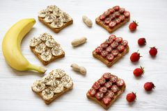 Vegetarian toasts with peanut butter, fruits and chia seeds on a white wooden table, low angle. Some ingredients. Healthy eating. Closeup. Selective focus Stock Images