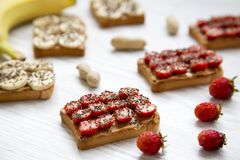 Vegetarian toasts with peanut butter, fruits and chia seeds on a white wooden table, side view. Some ingredients. Dieting concept. Close-up stock photos