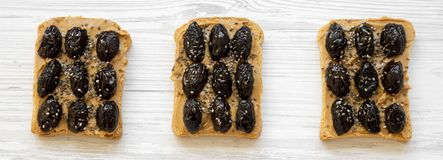 Vegetarian toasts with peanut butter, olives and chia seeds on a white wooden surface, top view. Healthy dieting royalty free stock photography