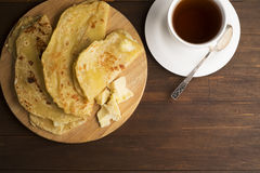Vegetarian tortilla with potatoes and butter. Decorated tea set laid out on a wooden Board and brown table Royalty Free Stock Photo