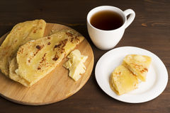 Vegetarian tortilla with potatoes and butter. Decorated tea set laid out on a wooden Board and brown table Royalty Free Stock Image