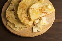 Vegetarian tortilla with potatoes and butter. Laid out on a wooden Board and brown table Royalty Free Stock Photo