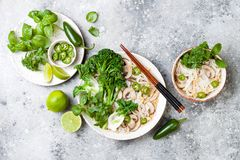 Vegetarian traditional Vietnamese soup Pho bo with herbs, rice noodles, broccolini, bok choy. Asian food concept. stock image