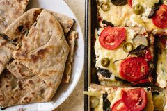 Vegetarian treats pizza with tomatoes, mozzarella and olives and naan with cheese and greens royalty free stock photography