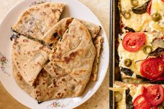 Vegetarian treats pizza with tomatoes, mozzarella and olives and naan with cheese and greens stock photos