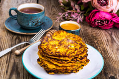 Vegetarian vegetable fritters with honey, tea in vintage cup stock photos