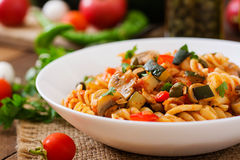 Vegetarian Vegetable pasta Fusilli with zucchini, mushrooms and capers in white bowl Stock Image