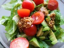 Vegetarian vegetable salad. Fresh salad flying to bowl in super slow motion. Avocado Tomato Salad.  stock image
