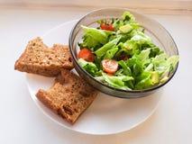 Vegetarian vegetable salad. Fresh salad flying to bowl in super slow motion. Avocado Tomato Salad.  royalty free stock photo