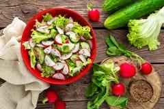 Vegetarian vegetable salad of radish, cucumbers, lettuce salad and flax seeds. Healthy  vegan food. Top view Stock Photo