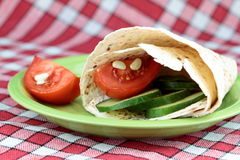 Vegetarian wrap. With cucumber and tomato on green plate Royalty Free Stock Images