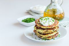 Vegetarian zucchini fritters or pancakes, served with greek yogu Stock Photo