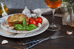 Vegetarian zucchini fritters served with fresh herbs, tomatoes a. Nd garlic. Romantic dinner with wine Stock Images