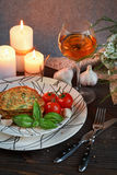 Vegetarian zucchini fritters served with fresh herbs, tomatoes a. Nd garlic. Romantic dinner with wine, candles and a flowers on a table Royalty Free Stock Photo