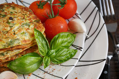 Vegetarian zucchini fritters served with fresh herbs, tomatoes a. Nd garlic. Selective focus Royalty Free Stock Image