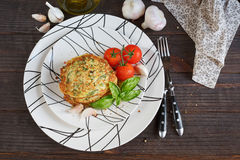 Vegetarian zucchini fritters served with fresh herbs, tomatoes a. Nd garlic. Selective focus Stock Photos