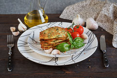 Vegetarian zucchini fritters served with fresh herbs, tomatoes a. Nd garlic. Selective focus Stock Image