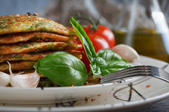 Vegetarian zucchini fritters served with fresh herbs, tomatoes a. Nd garlic. Selective focus Royalty Free Stock Photos