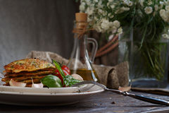 Vegetarian zucchini fritters served with fresh herbs, tomatoes a. Nd garlic. Selective focus Stock Images