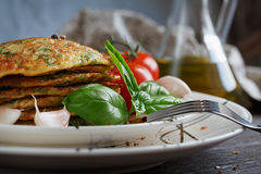 Vegetarian zucchini fritters served with fresh herbs, tomatoes a. Nd garlic. Selective focus Royalty Free Stock Images