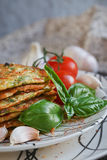 Vegetarian zucchini fritters served with fresh herbs, tomatoes a. Nd garlic. Selective focus Royalty Free Stock Photography