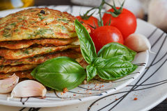 Vegetarian zucchini fritters served with fresh herbs, tomatoes a. Nd garlic. Selective focus. Close up Stock Photography