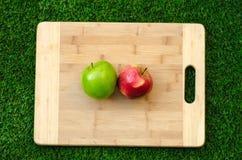 Vegetariani e cucinare sulla natura del tema: trovandosi sulle mele rosse e verdi di un tagliere su un fondo dell'erba Fotografia Stock Libera da Diritti