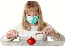 Vegetarianism. The girl in a medical mask tries to cut a tomato Stock Images
