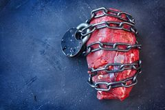 Free Vegetarianism. Vegan Food Concept With Piece Of Meat, Metallic Chain And Lock. Stock Photo - 155680330