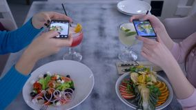 Vegetariankvinnavänner som använder smartphonen och tar fotoet av härlig mat för socialt massmedia under den sunda frukosten arkivfilmer