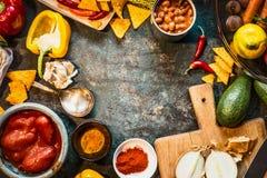 Vegetariano che cucina gli ingredienti per cucina messicana: fagioli inscatolati, pomodori sbucciati, paprica, peperoncino rosso, fotografie stock