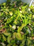Vegetariano che cucina nel selvaggio: Stufato dei broccoli con i funghi e la malva dello zucchini Immagine Stock