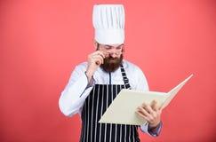 vegetariano Cuoco unico maturo con la barba Cottura sana dell'alimento Uomo del cuoco unico in cappello Ricetta segreta di gusto  immagine stock libera da diritti