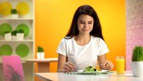 Vegetariano femminile che mangia il caff? di seduta dell'insalata fresca, vetro del succo d'arancia sulla tavola fotografia stock