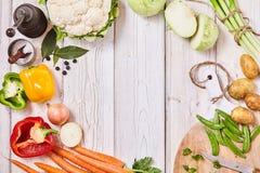 Vegetarianos frescos deliciosos que formam um quadro na madeira Fotografia de Stock