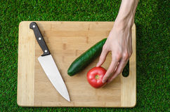 Vegetarians and cooking on the nature of the theme: human hand holding cucumber, tomato on a cutting board and a background of gre Stock Images