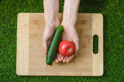 Vegetarians and cooking on the nature of the theme: human hand holding cucumber, tomato on a cutting board and a background of gre Stock Photo