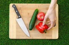 Vegetarians and cooking on the nature of the theme: human hand holding cucumber, tomato and red pepper on a cutting board and a ba Stock Photo