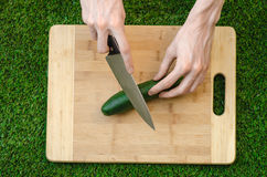 Vegetarians and cooking on the nature of the theme: human hand holding a knife and cucumber on a cutting board and a background of Royalty Free Stock Image