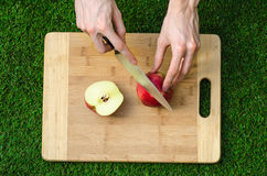 Vegetarians and cooking on the nature of the theme: human hand holding a knife and a red apple on the background of a cutting boar Stock Photos