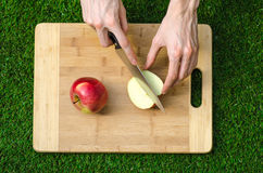 Vegetarians and cooking on the nature of the theme: human hand holding a knife and a red apple on the background of a cutting boar Royalty Free Stock Image
