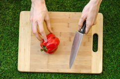 Vegetarians and cooking on the nature of the theme: human hand holding a red pepper and a knife on a cutting board and a backgroun Stock Photos