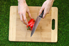 Vegetarians and cooking on the nature of the theme: human hand holding a red pepper and a knife on a cutting board and a backgroun Stock Photography