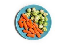 Vegetarier- und Vegetarierlebensmittel auf Weiß Schätzchen-Karotten getrennt Rosenkohl eine Platte Stockfotografie