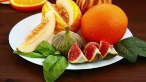 Vegetarisch dieet Op de lijst lig fruit: Vietnamese meloen, fig., kiwi, sinaasappelen, sap Close-up stock footage