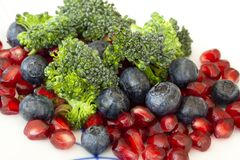 Vegetarisch ruw voedsel Salade van broccoli, granaatappelzaden en bosbessen een verscheidenheid van voedingsmiddelen Extreem clos royalty-vrije stock foto
