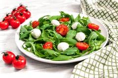 Vegetarisch voedsel en gezond levensstijlconcept - spring salade met kersentomaat, mozarellakaas en arugula op Royalty-vrije Stock Fotografie
