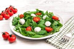 Vegetarisch voedsel en gezond levensstijlconcept - spring salade met kersentomaat, mozarellakaas en arugula op Royalty-vrije Stock Foto's